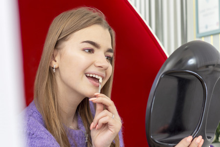 girl on the procedure of teeth whitening checks the color of the tone of the teeth looks in the mirror Stock Photo