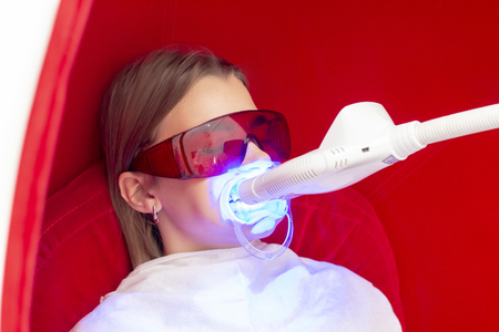 teeth whitening UV lamp with a special tool girl on teeth whitening procedure