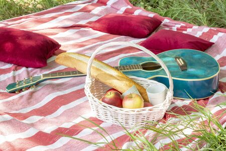 summer picnic basket with apples and guitar lie on a plaid with pillows heat Stock Photo