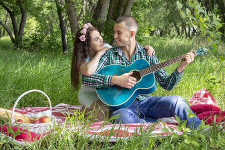 summer picnic, romance. the guy plays his girlfriend on the guitar, smile emotionally. happiness