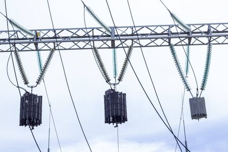 Power Tower. High voltage lines and power pylons. City power substation, close-up, transformer with high-voltage wires. High voltage power lines installing on high electric post connected Banco de Imagens