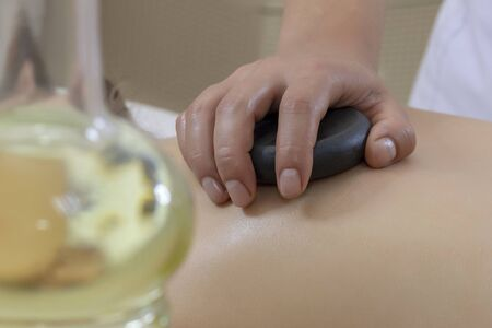 Spa Hot Stone Massage. Stone treatment. Woman getting a hot stone massage at a day spa