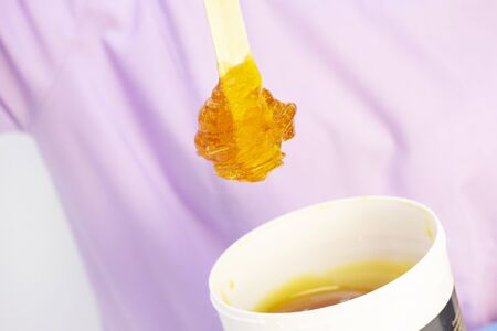 Liquid sugar for skin epilation. Close up shot. depilation and beauty concept - sugar paste or wax honey for hair removing with wooden waxing spatula sticks