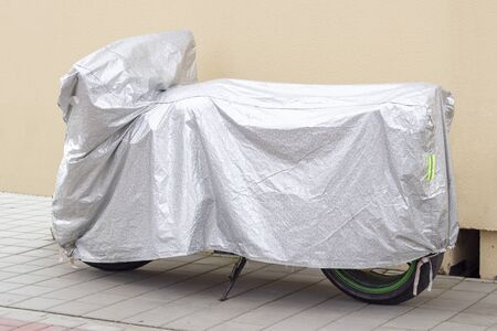 motorcycle parking on the side of the street with plastic sheet covering. motorcycle stands against a beige wall