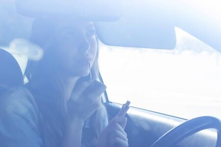 driver girl paints her lips in a car, looks in the mirror in the driver's seat. photo taken through the windshield of a car