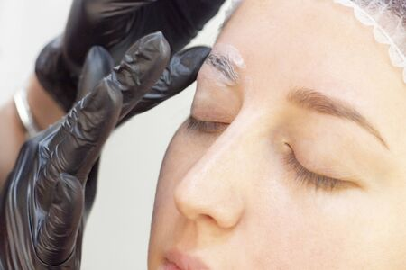eyebrow shaping in a beauty salon. Shampoo is applied to the girl's eyebrows to remove excess fat and clean hair. before applying eyebrow dye. eyebrow master Stock fotó - 131786947