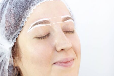 eyebrow dyeing. beauty saloon. the girl lies with her eyes closed on the eyebrow dyeing procedure. preparation of eyebrows for painting. applying cream around the eyebrows.
