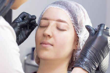 eyebrow dyeing. beauty saloon. the girl lies with her eyes closed on the eyebrow dyeing procedure. preparation of eyebrows for painting. applying cream around the eyebrows using thread.