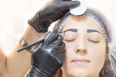 eyebrow dyeing. beauty saloon. the girl lies with her eyes closed on the eyebrow dyeing procedure. The eyebrow master applies brush to the eyebrows of the client. Stock Photo