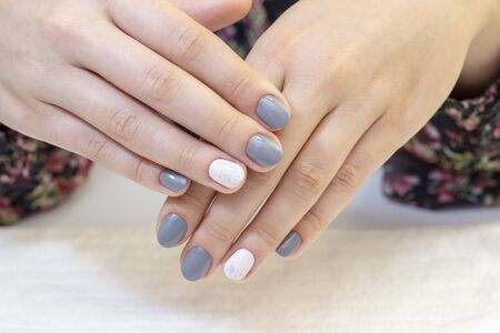 Stylish trendy female manicure. Beautiful young womans hands. gray and white nail polish