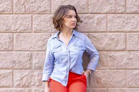female portrait. beautiful young girl stands on a background of a beige brick wall with stucco. red pants and a denim shirt. beige background Stock Photo