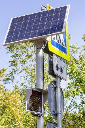 Traffic light working on solar power. Solar panel powering digital display of a traffic light. vertical photo