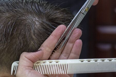 The hands of young barber making haircut to attractive man in barbershop. mens hair cutting scissors in a beauty salon Stock Photo