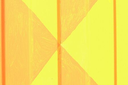 Texture of a profiled metal sheet painted in yellow color with orange abstract triangles