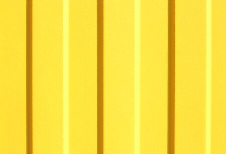 Texture of a profiled metal sheet painted in yellow color. shadow