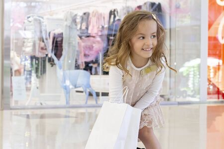 shopping. discounts. little shopaholic girl. girl with bags in hands. white bags with copyspace. the delight of shopping. shopping center, shopping. emotions