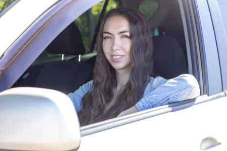Young woman driving her car. Attractive young girl driver in new car