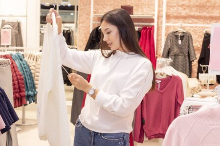 shopping girl. a beautiful girl with long dark hair is in a clothing boutique, chooses a sweater for herself. Looks at price tags and checks quality. Stock Photo
