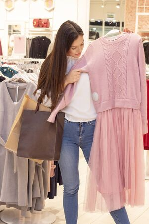 shopping girl. a beautiful girl with long dark hair is in a clothing boutique, chooses a dress for herself. puts a dress on herself. vertical photo. in the hands of a bag Stock Photo