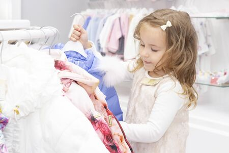 shopping. discounts. little girl shopaholic. girl delighted with beautiful jackets, chooses warm clothes. shopping center, shopping. emotions