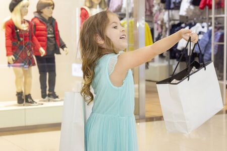 shopping. discounts. little girl shopaholic. girl with shopping bags in hands. white bags copyspace. shopping center, shopping. emotions