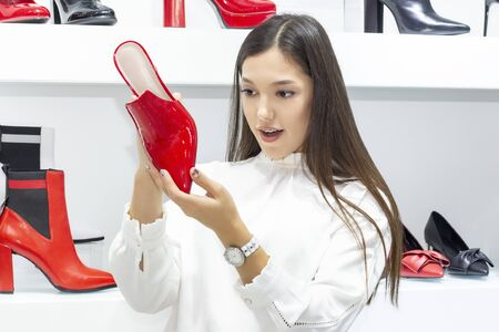 girl buys shoes, a boutique selling shoes. beautiful girl is shopping. on the background of a girl shelves with shoes. Red shoes. the girl has braces on her teeth. Stock Photo