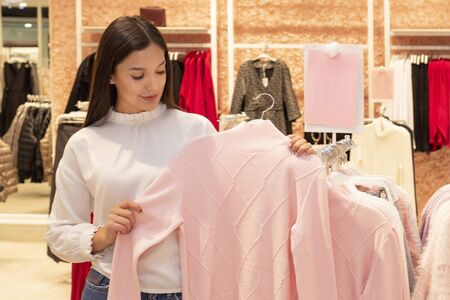 shopping girl. a beautiful girl with long dark hair is in a clothing boutique, chooses a sweater for herself. Looks at price tags and checks quality. copyspace