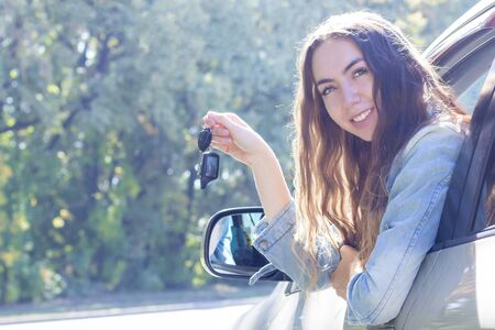 Young woman driving her car. Attractive young girl driver in new car . girl bought a car. shows the keys to a new car