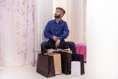young man with a bunch of bags is sitting in the fitting room and waiting. the girl in the dressing room tries on outfits, the guy shows on time. tired of waiting. shopping. black Friday.