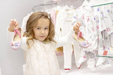 shopping. discounts. little girl shopaholic. girl chooses shoes for her dress. shopping center, shopping. emotions