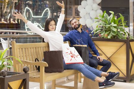 couple on shopping. the girl enjoys shopping and discounts. black Friday. a girl and a guy are sitting in a shopping center with shopping bags Stock Photo