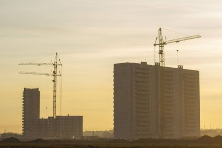 construction of multi-storey residential buildings. construction cranes. The construction of a new area in the wasteland. photo taken at dawn, natural sunny tinting.