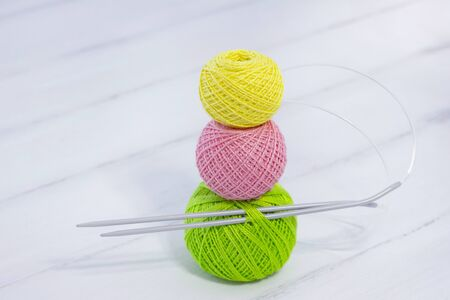 colored balls for knitting and knitting needles lie on a white wooden background. copyspace. creation. green, yellow and pink threads. snowman shaped threads