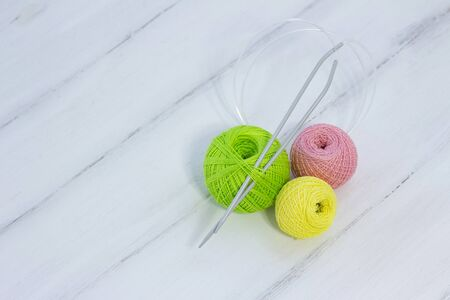 colored balls for knitting and knitting needles lie on a white wooden background. copyspace. creation. green, yellow and pink threads.
