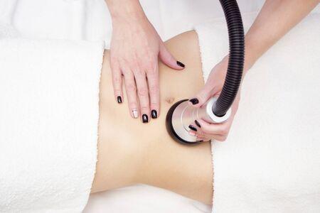 procedimiento de eliminación de la celulitis en el abdomen femenino, masaje de cavitación del vientre. Masaje ultrasónico para adelgazar. Corrección de figura femenina sin intervención quirúrgica. Primer plano de la barriga. Foto de archivo