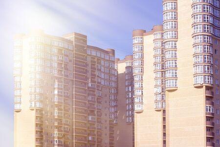 Background of multi-storey buildings in panoramic glazed balconies on high floors. sun exposure.