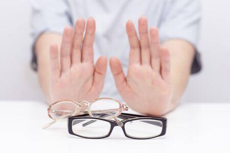 Refusal of glasses for sight. hands refuse glasses. cross on glasses. Vision improvement, laser vision correction.