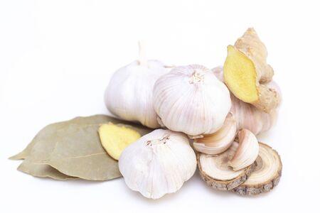 aglio essiccato, zenzero e alloro su uno sfondo bianco. concetto di medicina tradizionale. spicchi d'aglio