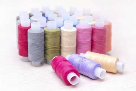 threads on spools of different colors lie on a light wooden table. Three spools of thread are lying. Sewing and atelier hobby concept. Stock fotó