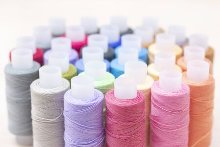 threads on spools of different colors lie on a light wooden table. Sewing and atelier hobby concept.