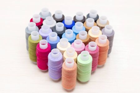 abstract background. spools of sewing thread in different colors. are on the table in the shape of a heart. sewing love concept.
