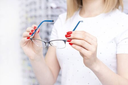 Optician in the store holds glasses. Eye doctor with lenses. Professional optometrist with a lot of points. The interior of the store. Fixing or comparing different options with glasses.