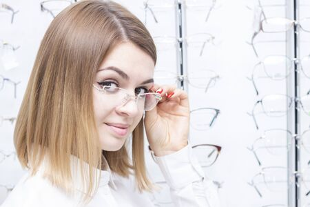 healthcare, people, vision and vision concept. Girl smiling trying on glasses in the store.