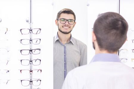 healthcare, people, vision and vision concept. men smiling trying on glasses in the store.