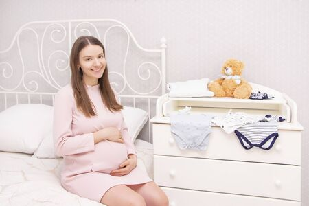 A pregnant beautiful girl is sitting on the bed and her hands are on her stomach. On the changing table are things for the newborn. Archivio Fotografico