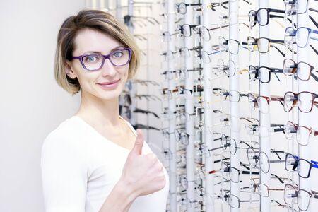 Mädchen mit Brille für das Sehvermögen. Brille in einem Optikergeschäft ausprobieren. Zufriedenes Mädchen zeigt wie.