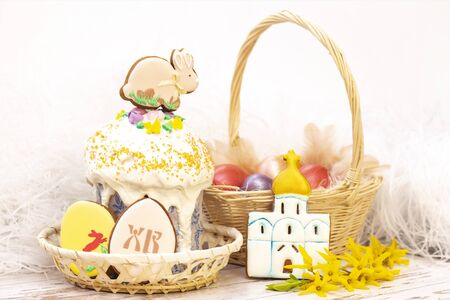 Easter holiday. Colored eggs in a basket. Easter gingerbread bunny on the easter cake. Easter gingerbread cookies in the form of eggs and a temple. on a light wooden background. translation of Russian letters: CR (Christ is risen)