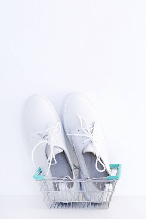 White new sneakers in a shopping basket on a white background. vertical photo Stock Photo