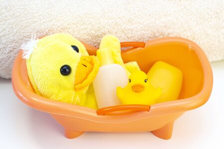 baby hygiene and bath items, shampoo bottle, baby soap, towel, yellow duck rubber toy, cotton pads and ear sticks, comb. in the bath Banque d'images