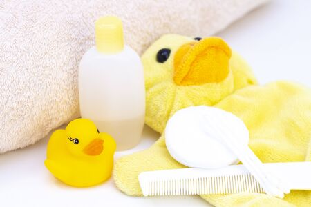 baby hygiene and bath items, shampoo bottle, baby soap, towel, yellow duck rubber toy, cotton pads and ear sticks, comb.